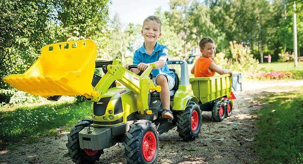 bambini giocano su un trattore a pedali